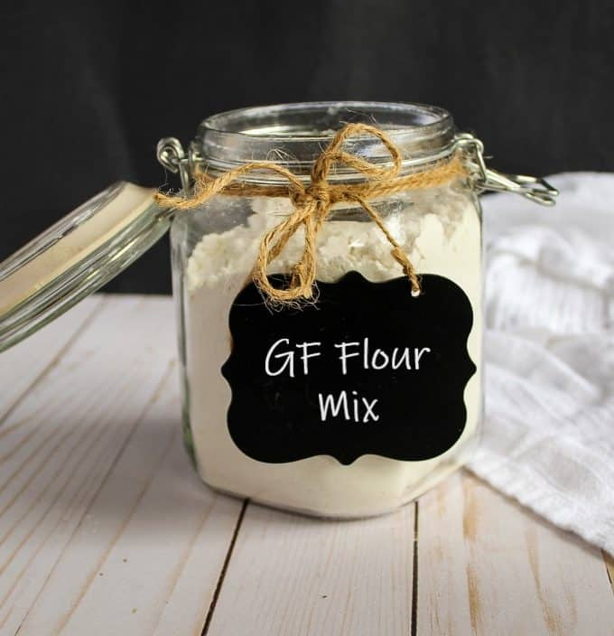glass jar of gluten free flour mix sitting on a counter.