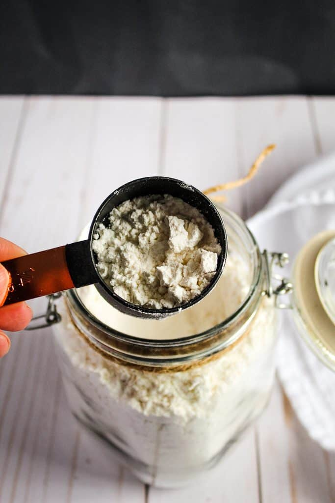 gluten free flour mix in a glass jar measured in a cup.