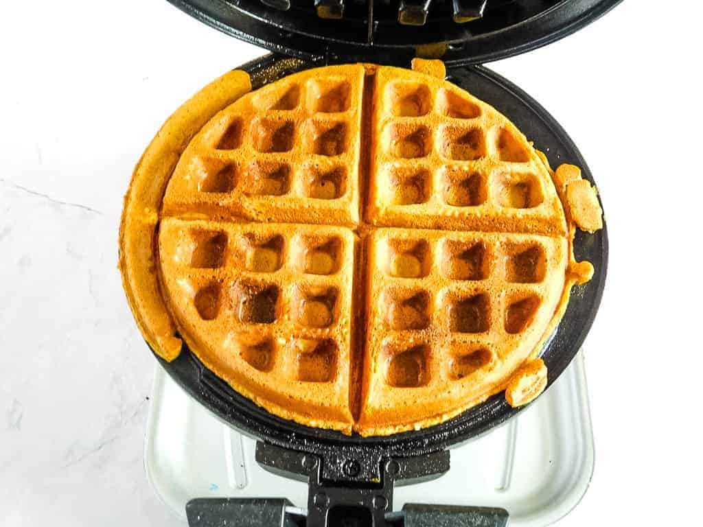 a cooked waffle in a black waffle iron