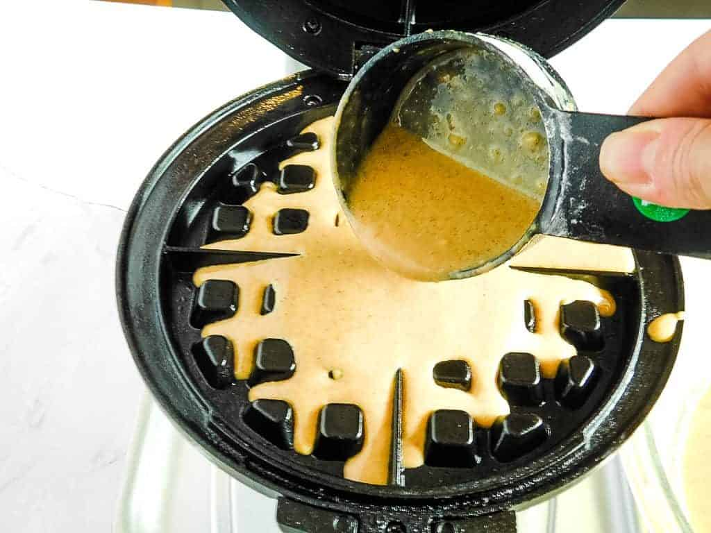 gluten free pumpkin waffle batter being poured into a waffle iron