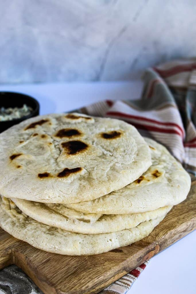 Stack of gluten free pita bread on a wooden cutting board