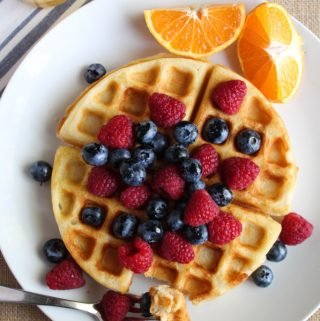 gluten free belgian waffles on a white plate with fruit