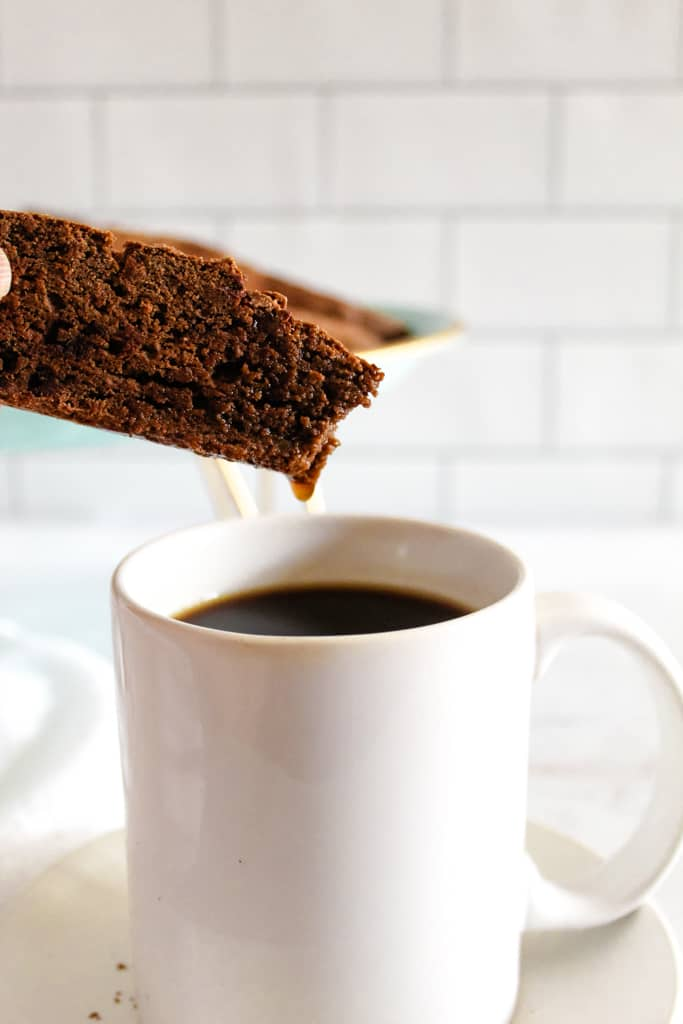 side shot of coffee dripping off biscotti
