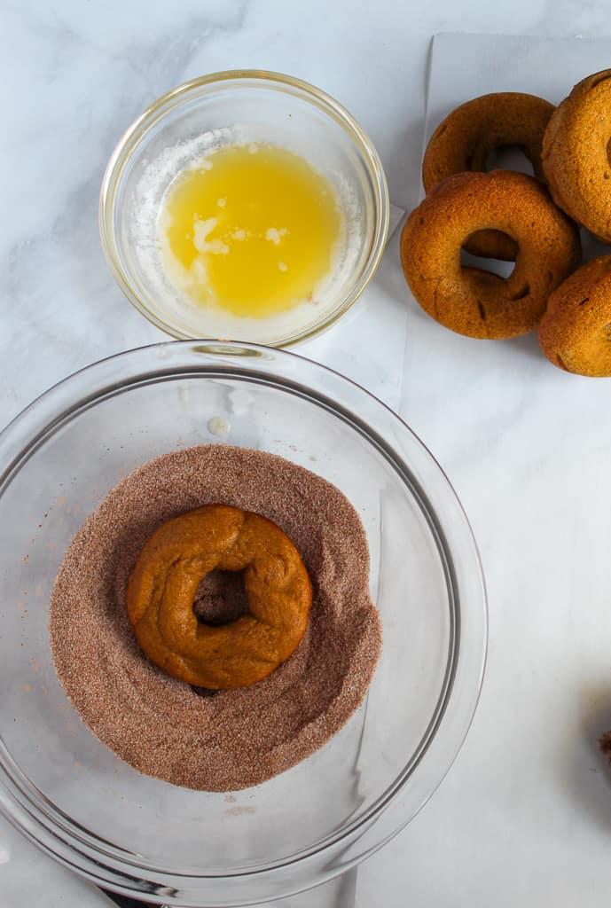 gluten free pumpkin donuts dipped in sugar in a glass bowl