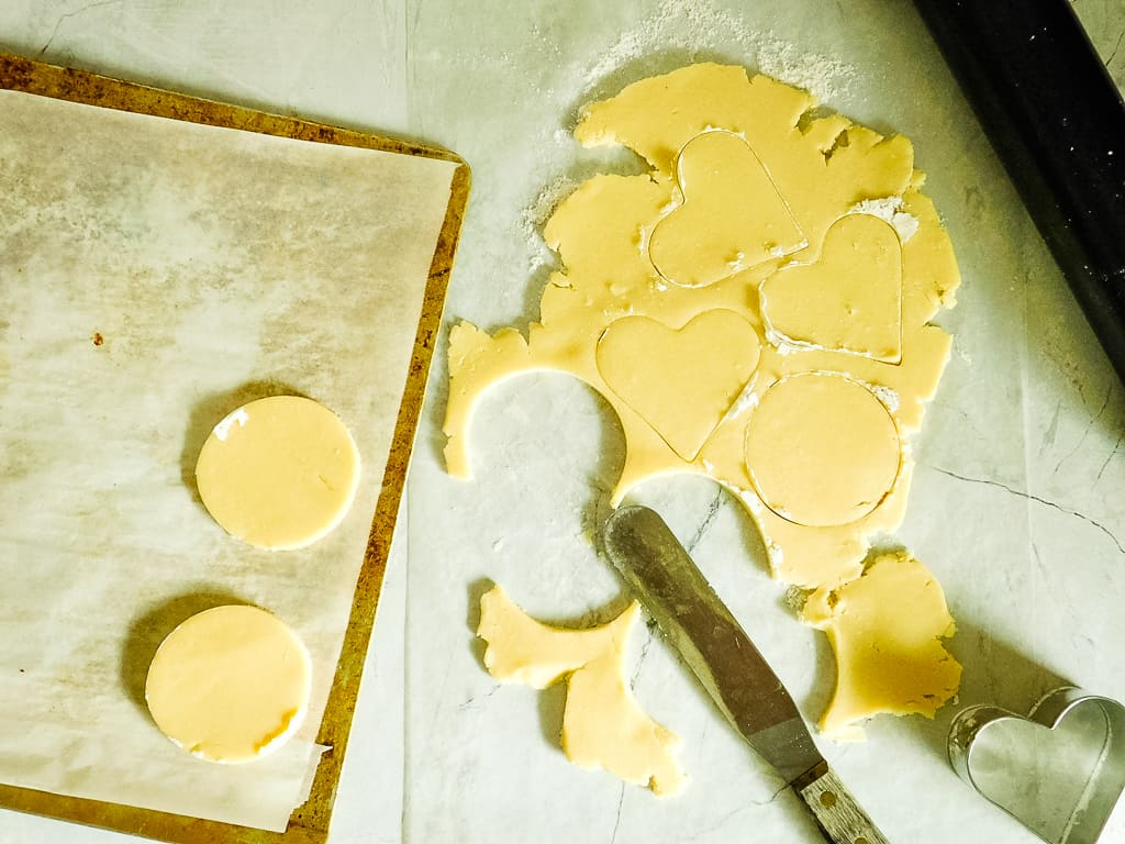overhead shot of cookie dough rolled out and cut with cutters
