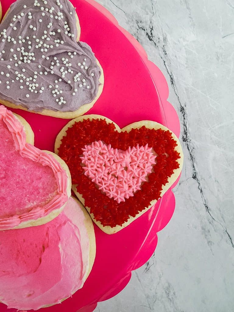 valentine decorated cookies on a pink platter