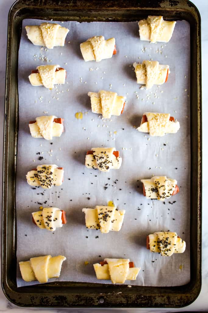 gluten free pigs in a blanket rolled on a baking pan