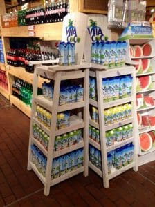 Two loaded open display shelves with coconut water, a gluten free option.