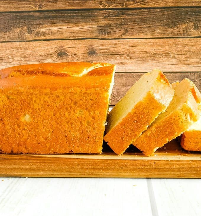 sliced loaf of gluten free white bread on a brown wooden cutting board