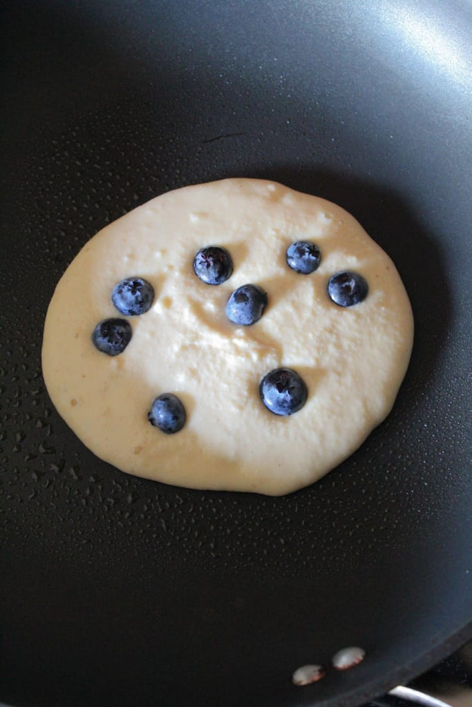 gluten free blueberry pancakes cooking in a skillet