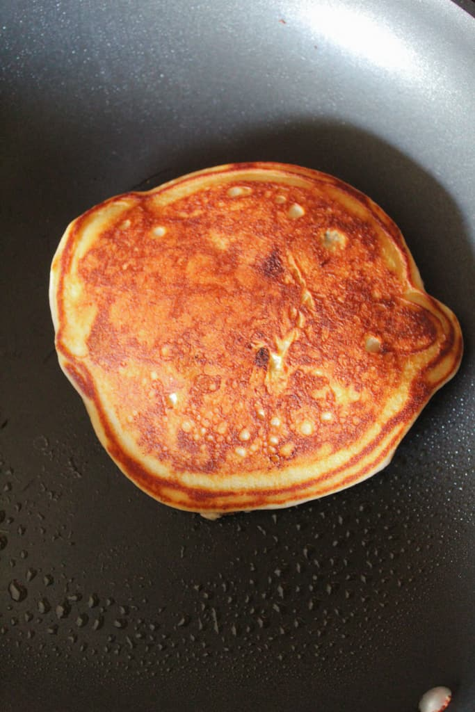 gluten free blueberry pancakes flipped over in the skillet