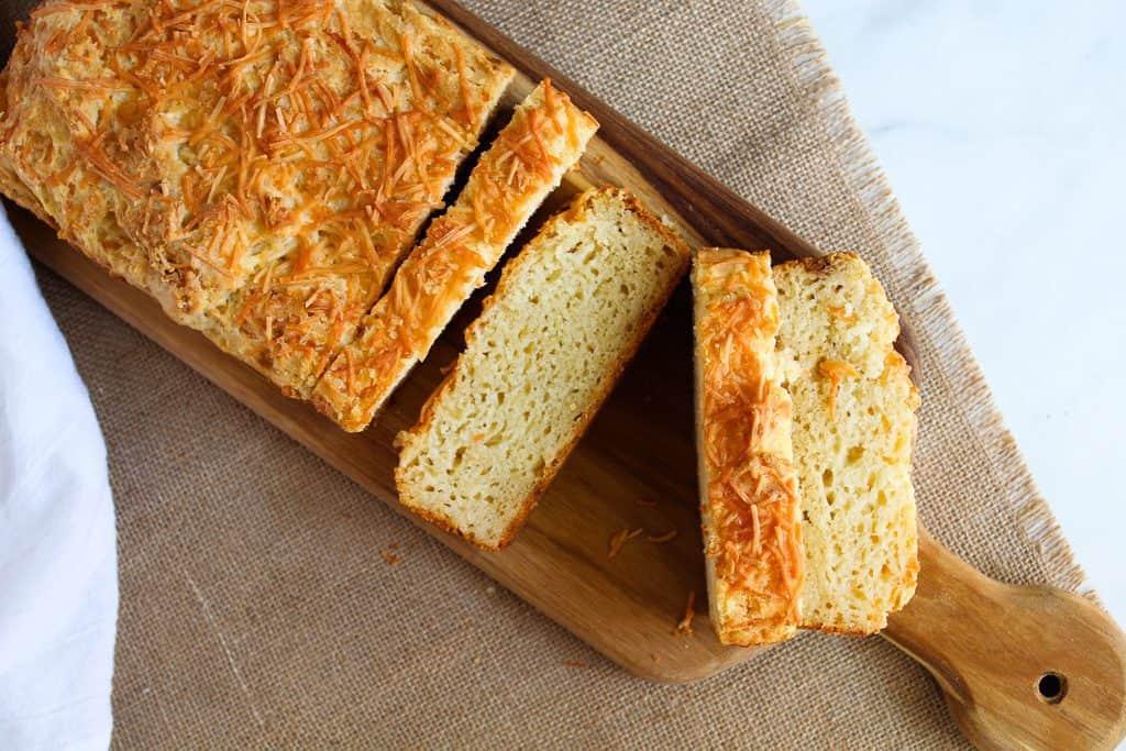 sliced loaf of gluten free garlic bread on a wooden cutting board