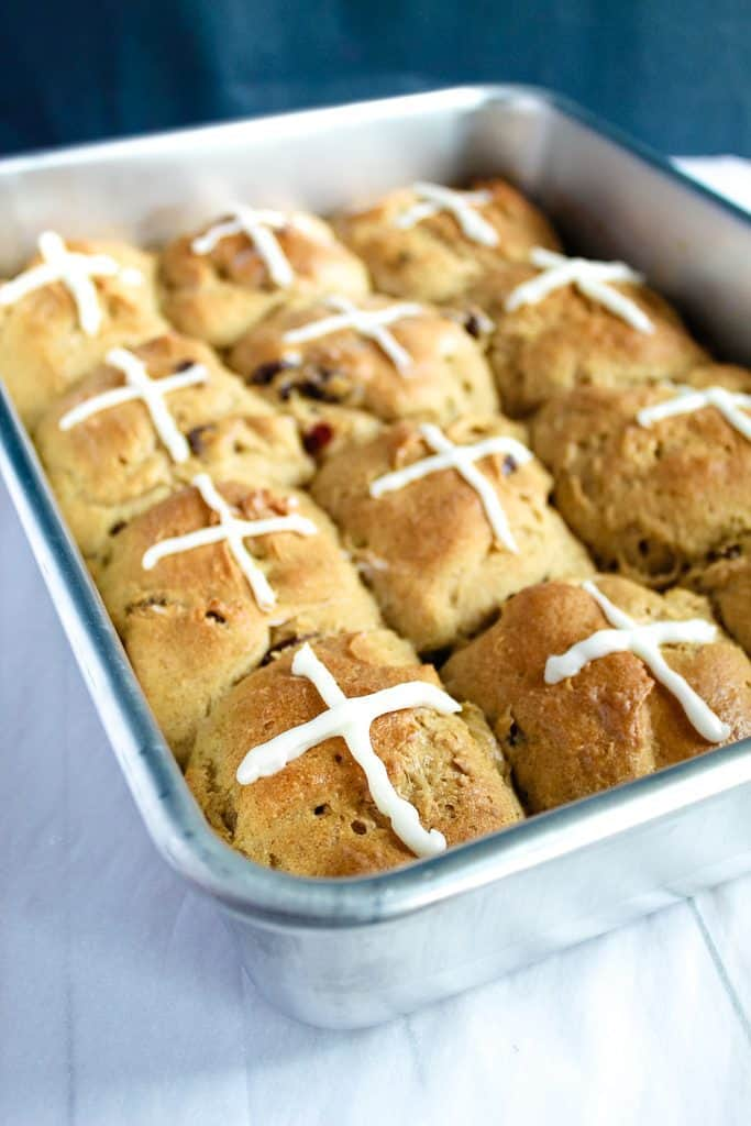 gluten free hot cross buns with glaze in a baking pan