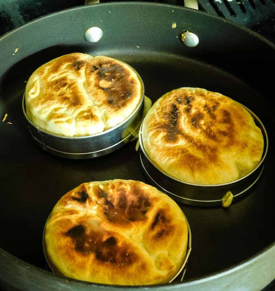 english muffins cooking in a black cook pan