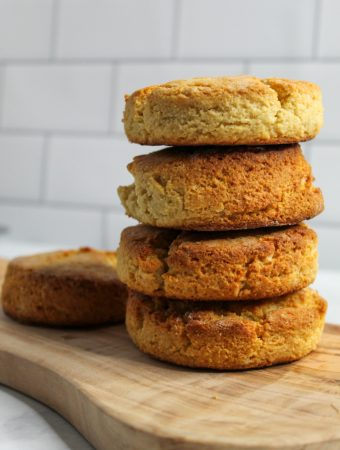 Almond Flour Biscuits stacked on a wooden cutting board