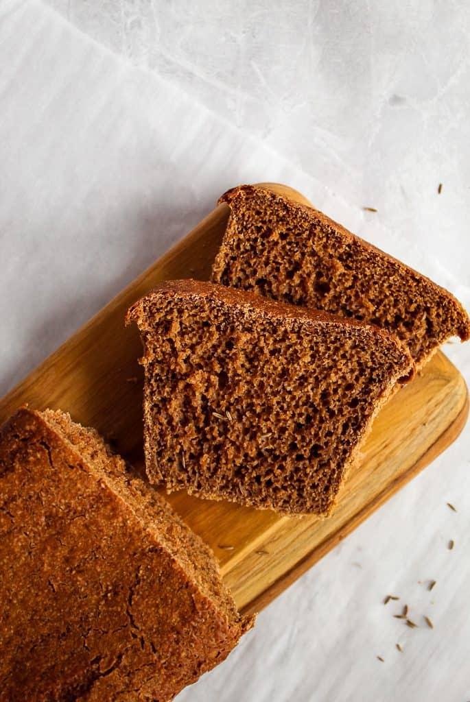 Gluten free pumpernickel bread slices on a wooden cutting board