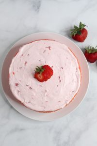 gluten free strawberry cake frosted on a platter