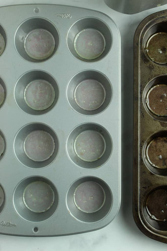 muffin tins prepped for baking rolls