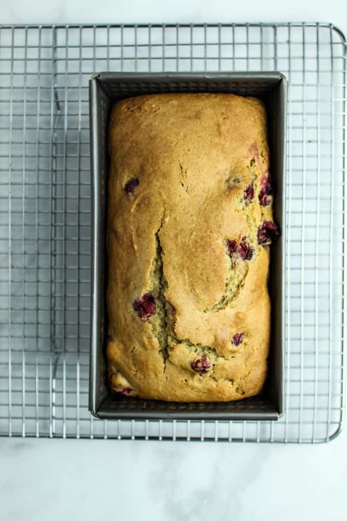 baked loaf of gluten free cranberry orange bread on a wire rack