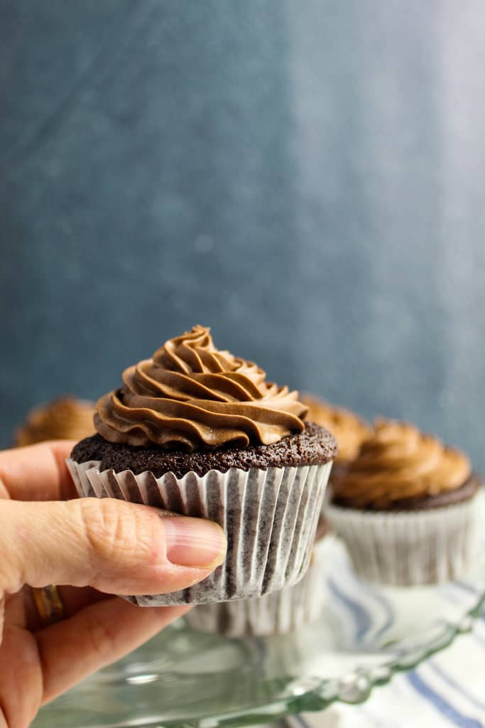 side shot of a hand holding a cupcake