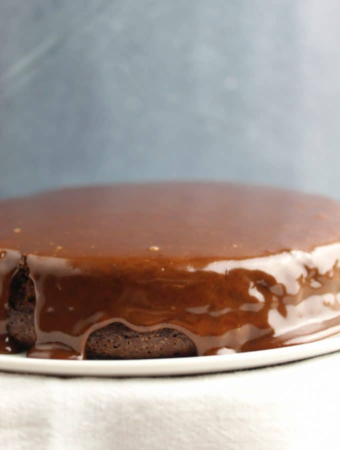 shot of chocolate ganache dripping don a cake