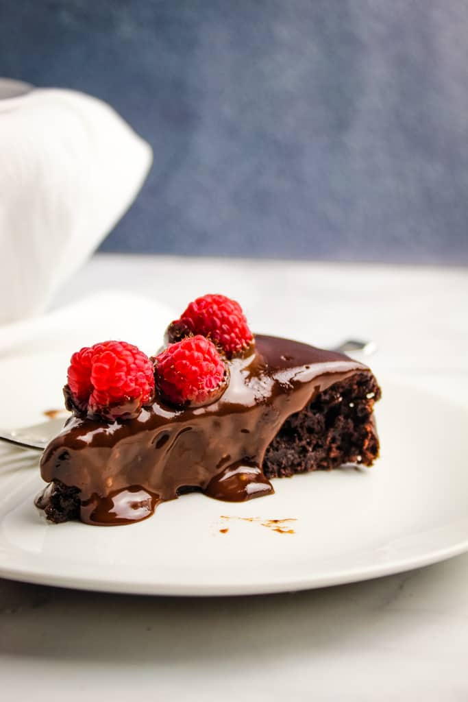 slice of flourless chocolate cake topped with raspberries